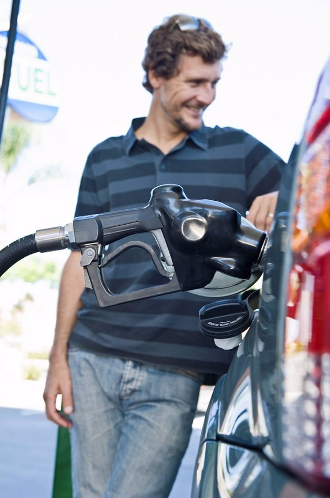 Stock Photo: 1654R-32151 Smiling man refueling car at natural gas station