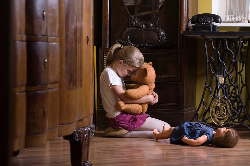 Stock Photo: 1654R-33856 Girl embracing teddy bear on floor in home
