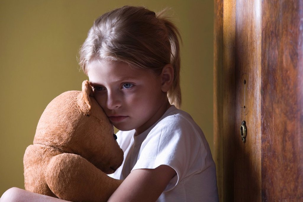 Girl embracing teddy bear in home : Stock Photo