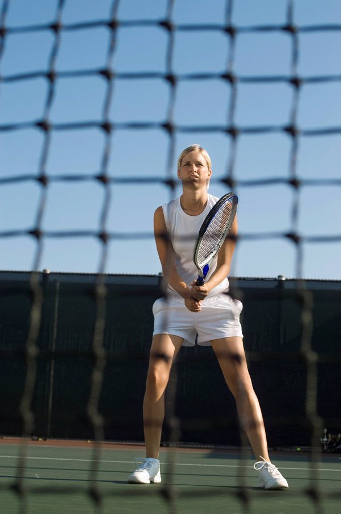Stock Photo: 1654R-3498 Tennis Player standing holding racket near net low angle view