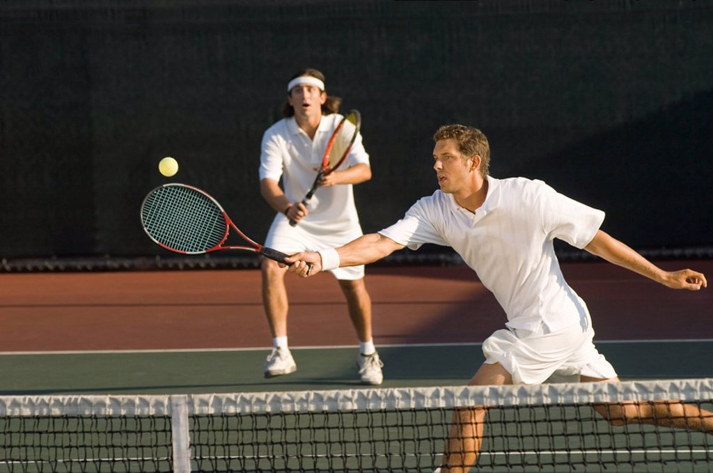 Tennis Player stretching Swinging at Ball near tennis net doubles partner standing behind : Stock Photo