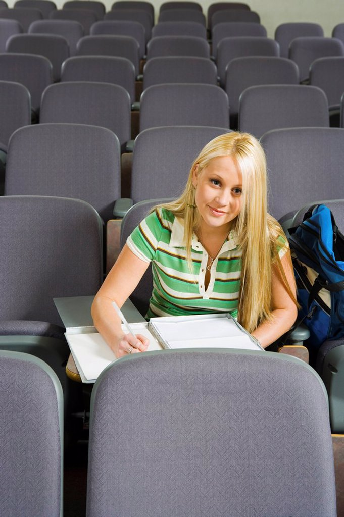 Stock Photo: 1654R-3646 Female student sitting alone in lecture hall portrait