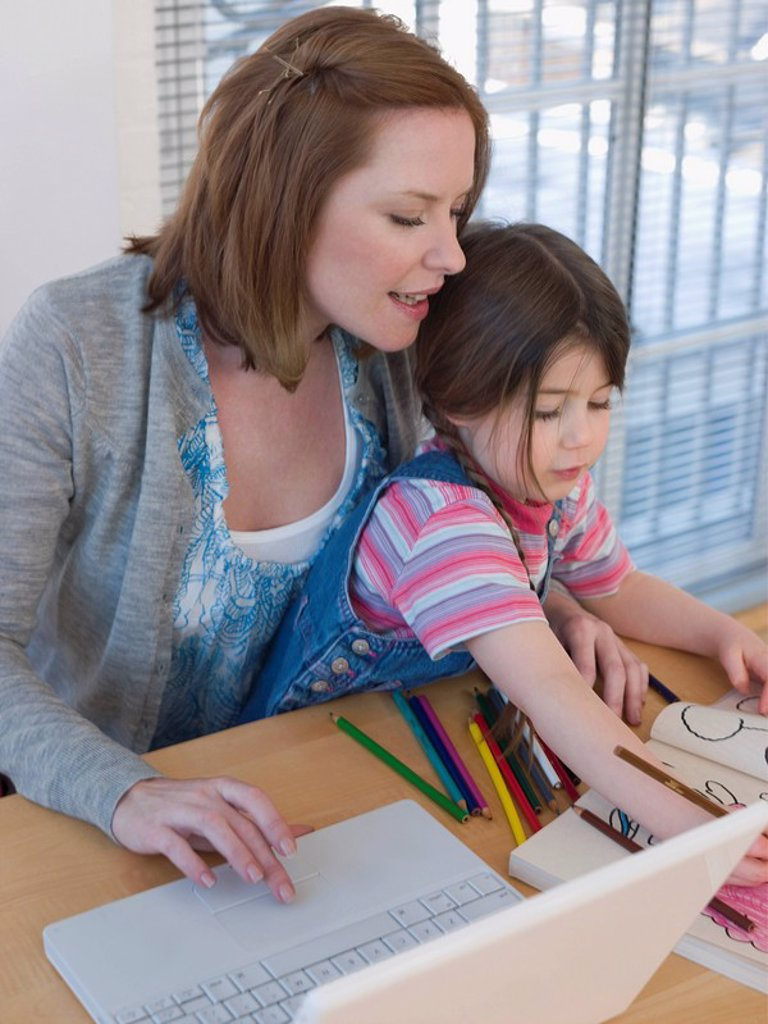 Mother Using Laptop While Daughter Colors : Stock Photo