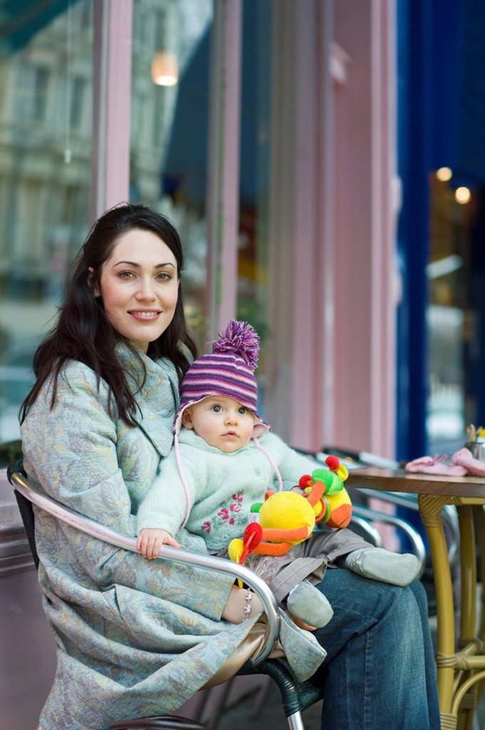 Mother with baby on her laps sitting outside cafe : Stock Photo