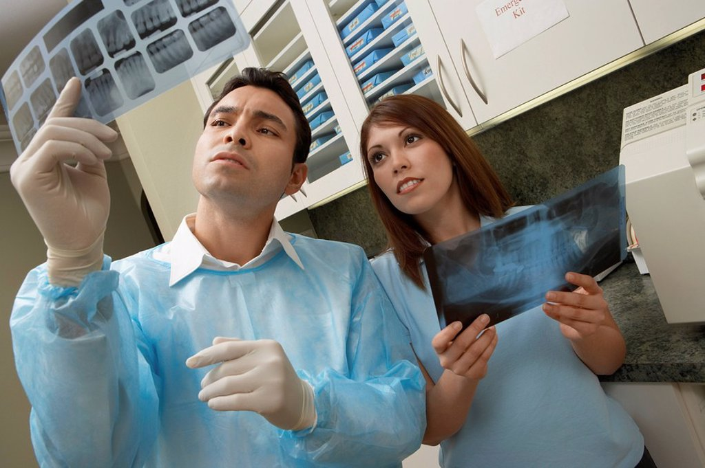 Dentist and hygienist examining X_rays in laboratory : Stock Photo