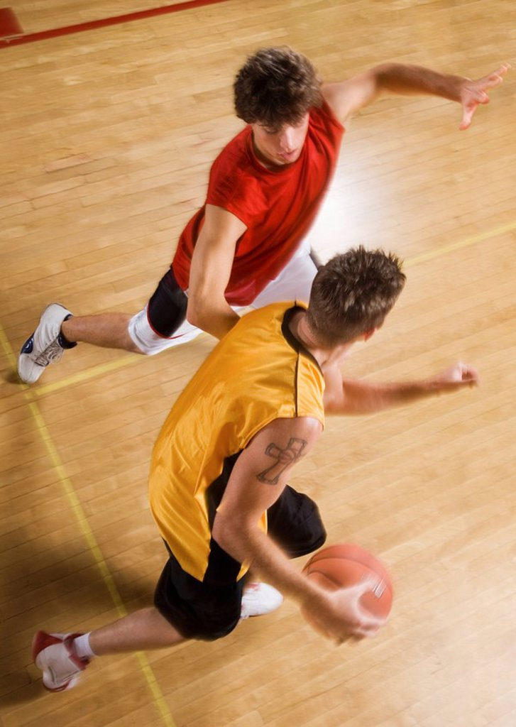 Stock Photo: 1654R-3875 Two young men playing basketball on indoor court