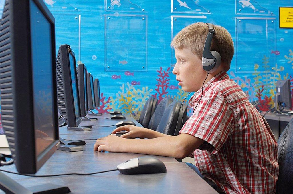 School boy wearing headphones in computer room : Stock Photo