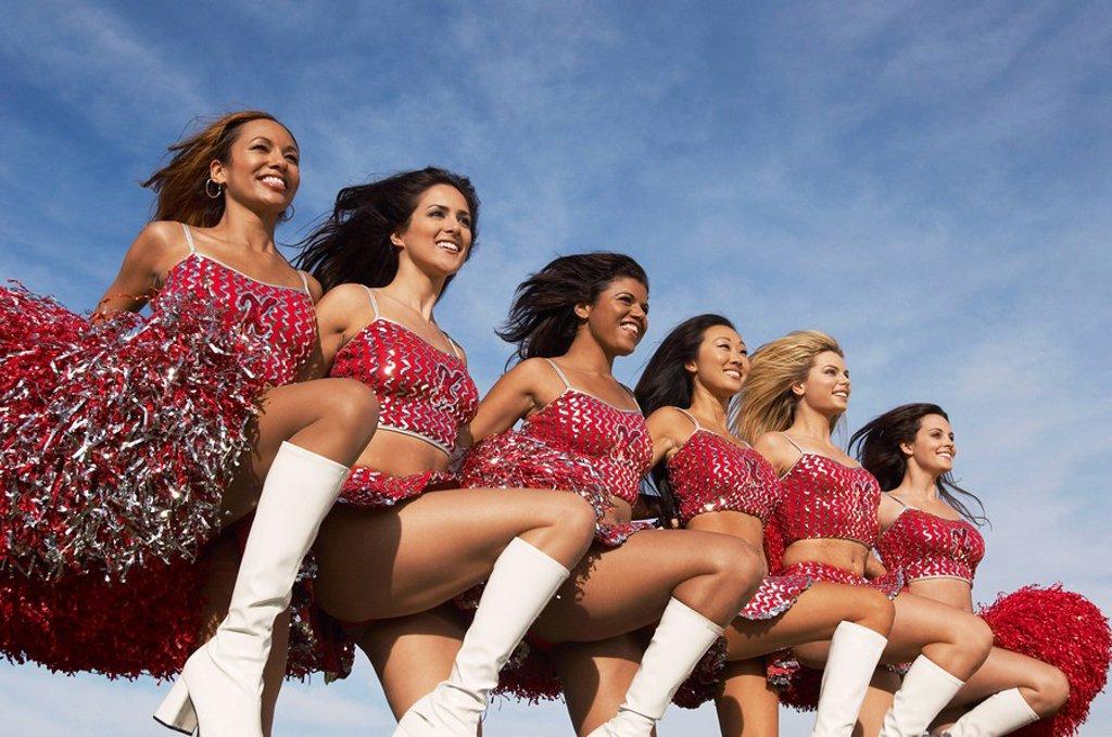 Cheerleaders in a row kicking legs : Stock Photo