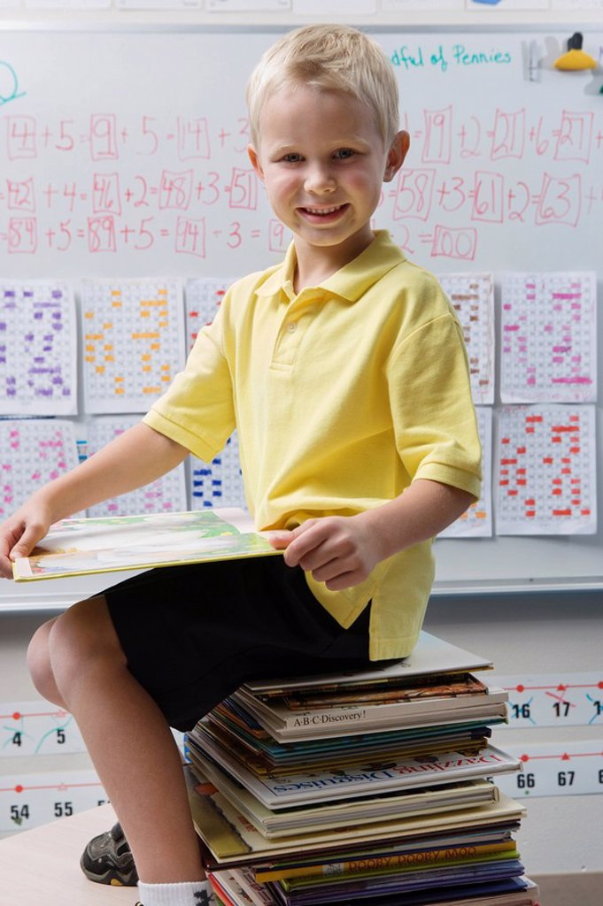 Stock Photo: 1654R-39710 Schoolboy Sitting on a Stack of Books