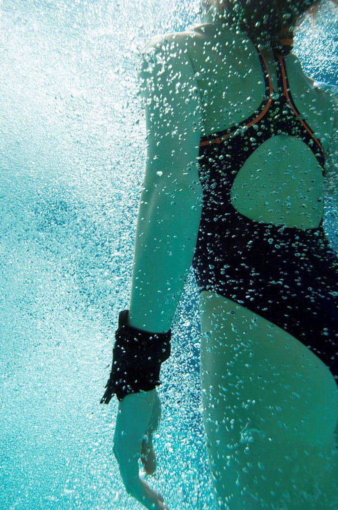 Stock Photo: 1654R-3986 Woman coming up for air underwater