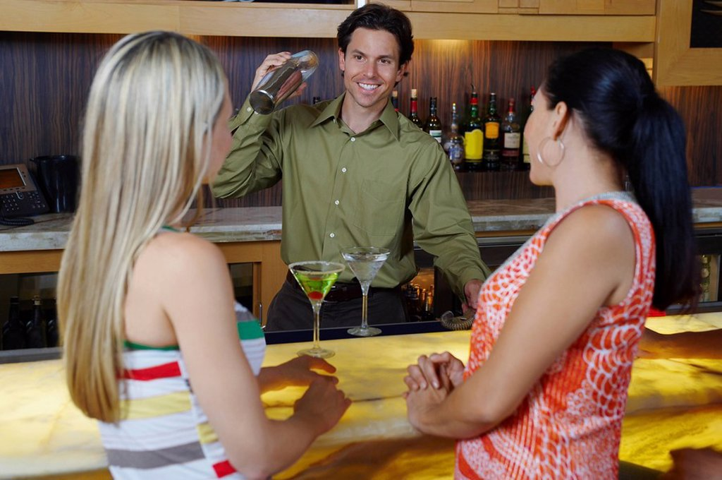 Stock Photo: 1654R-40566 Bartender Mixing Drinks for Women at Bar