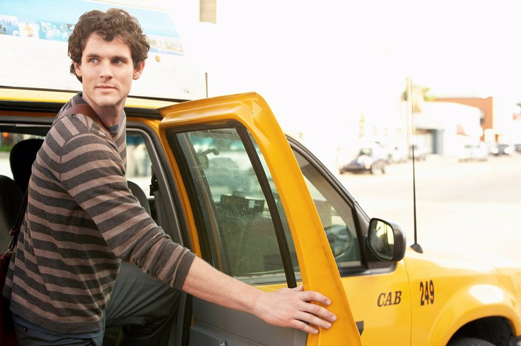 Man exiting taxi in street : Stock Photo