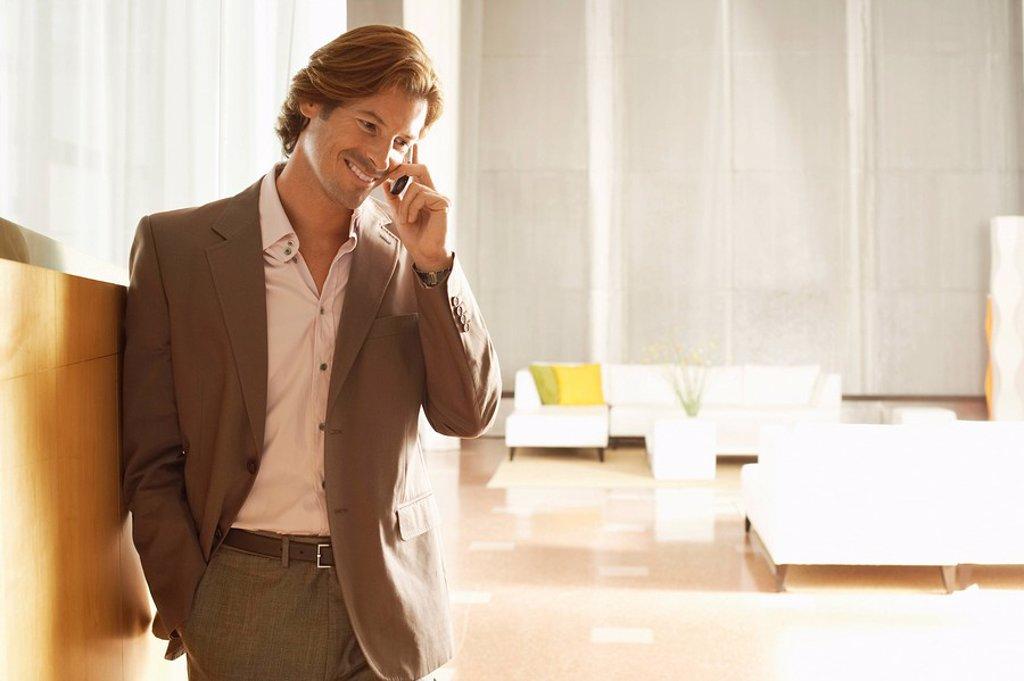 Businessman using mobile phone indoors : Stock Photo
