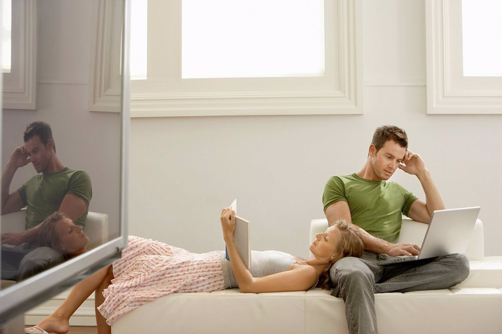 Couple relaxing together on sofa man using laptop woman reading : Stock Photo