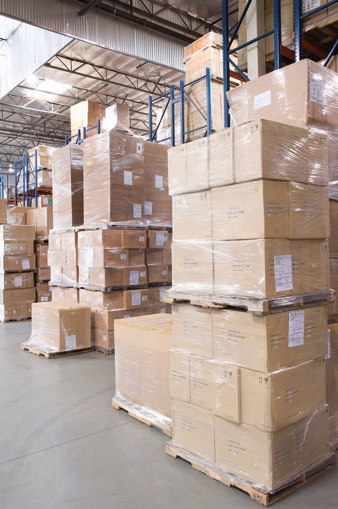 Cardboard boxes stacked in distribution warehouse : Stock Photo