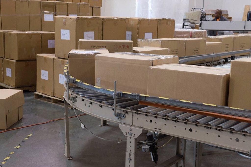 Cardboard boxes on conveyor belt in distribution warehouse : Stock Photo