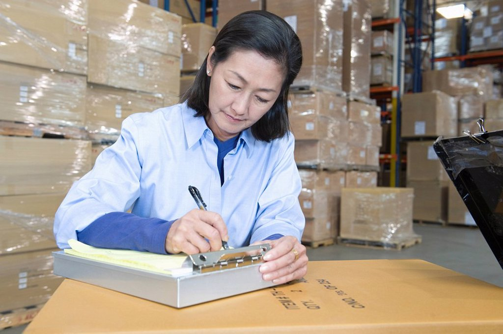 Woman making notes in distribution warehouse : Stock Photo