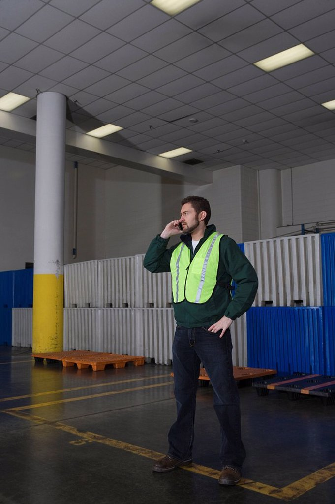 Stock Photo: 1654R-42140 Man standing in factory using telephone