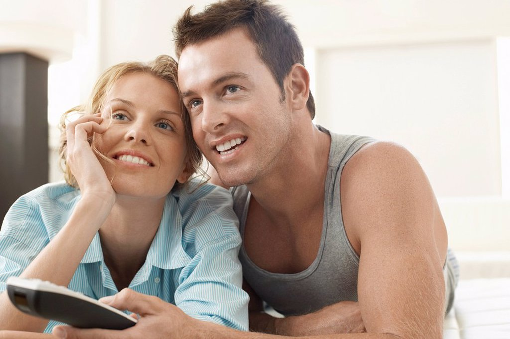 Couple on bed watching television man holding remote control : Stock Photo