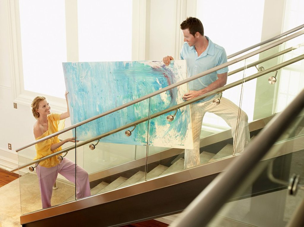 Couple moving modern painting up stairs elevated view : Stock Photo