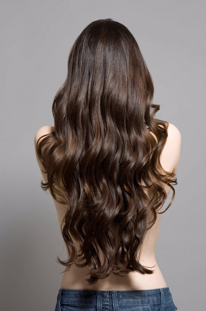 Stock Photo: 1654R-42516 Woman with long brown wavy hair rear view