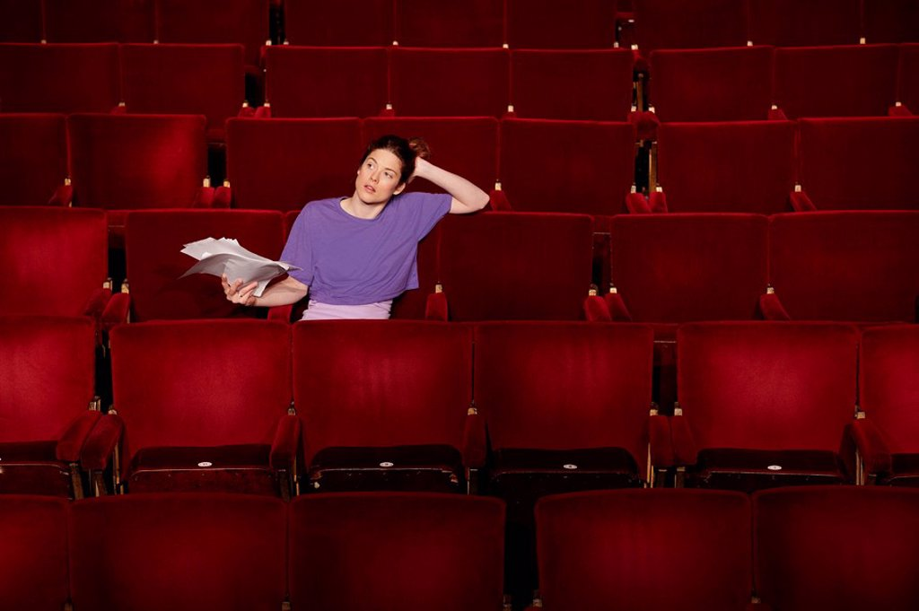 Young woman sitting in theatre stalls : Stock Photo