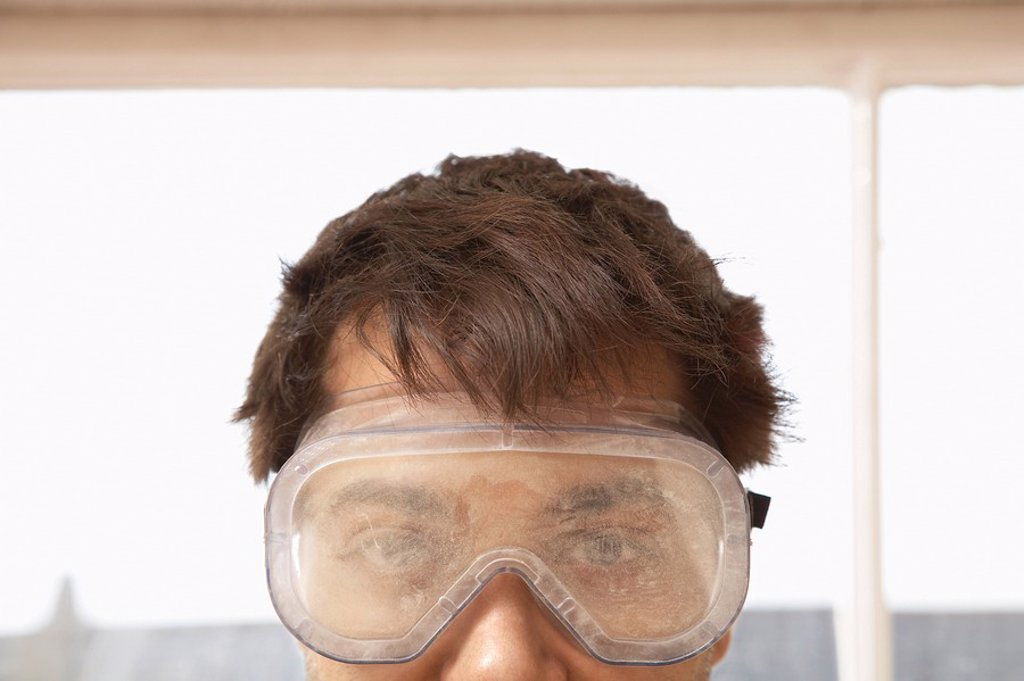 Stock Photo: 1654R-4304 Man wearing protective eye goggles indoors close up high section