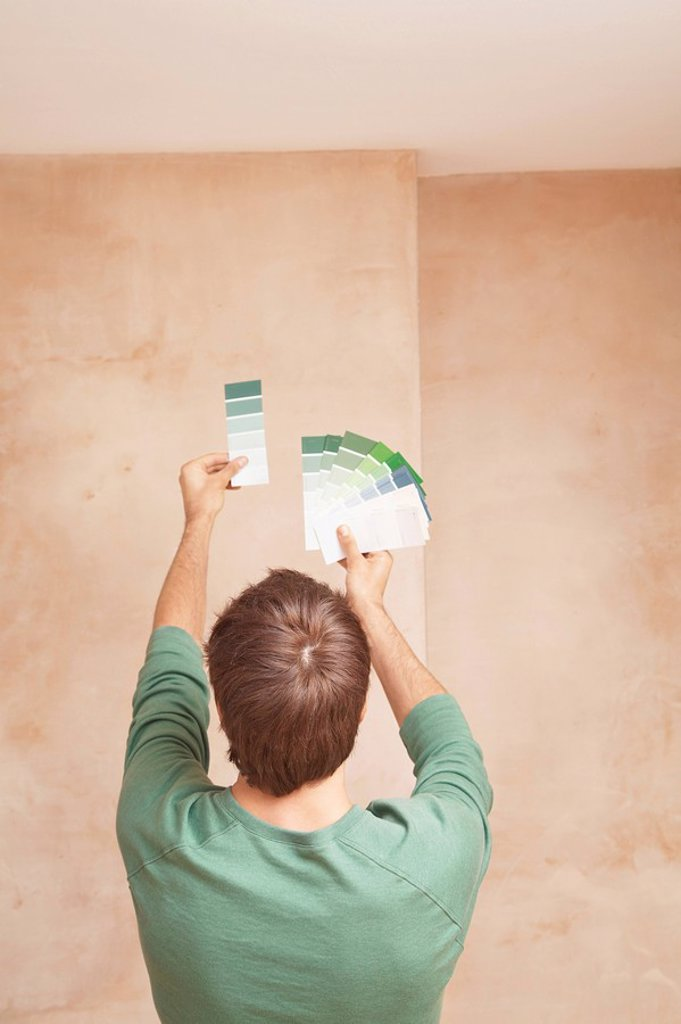 Man looking at paint colour swatches in unrenovated room back view : Stock Photo