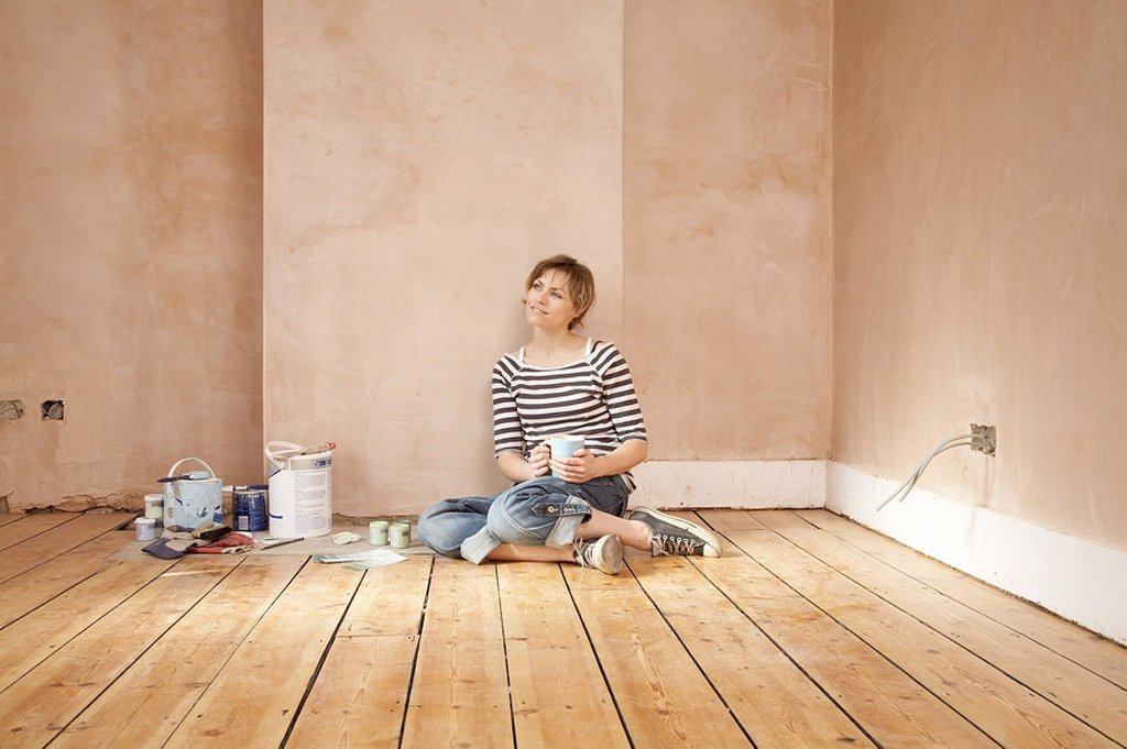 Stock Photo: 1654R-4315 Woman sitting on floor of unrenovated room holding coffee mug