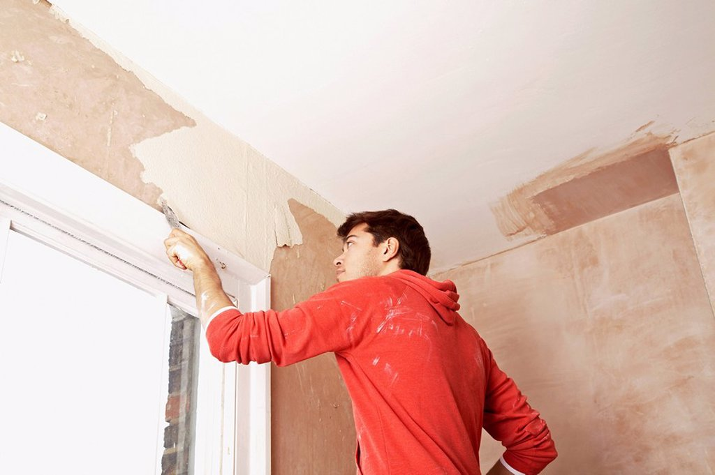 Man scraping paint off wall in unrenovated room low angle view : Stock Photo