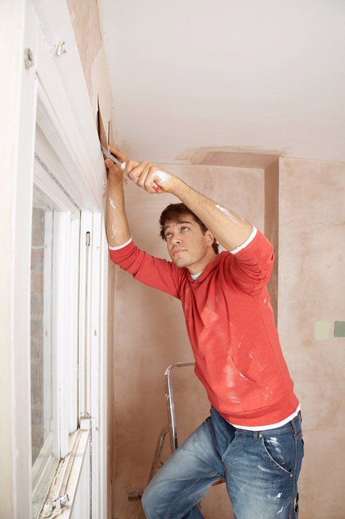 Man preparing wall of unrenovated room : Stock Photo
