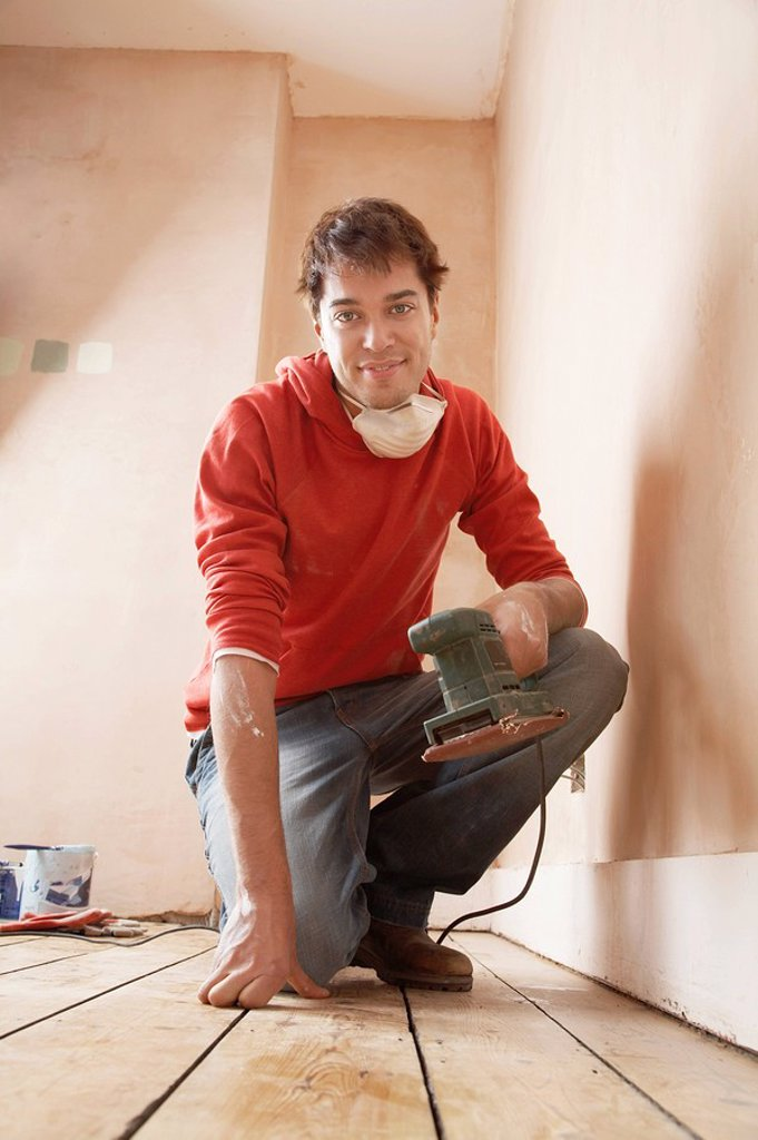 Stock Photo: 1654R-4332 Man holding sanding tool in unrenovated room portrait