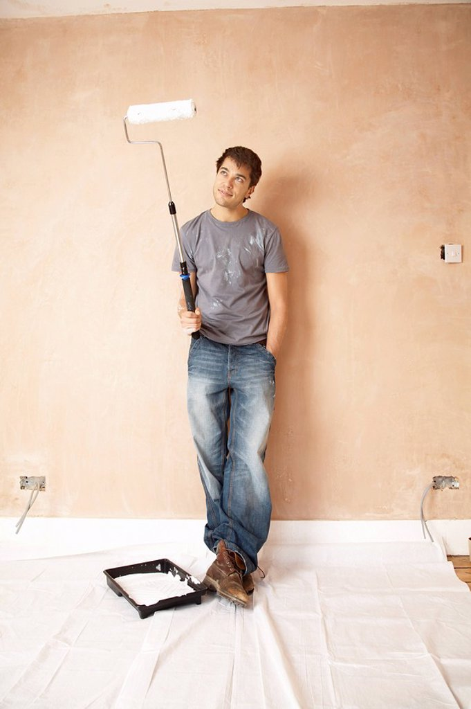 Man standing with paint roller in unrenovated room portrait : Stock Photo