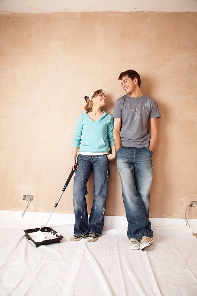 Couple standing with paint roller in unrenovated room : Stock Photo