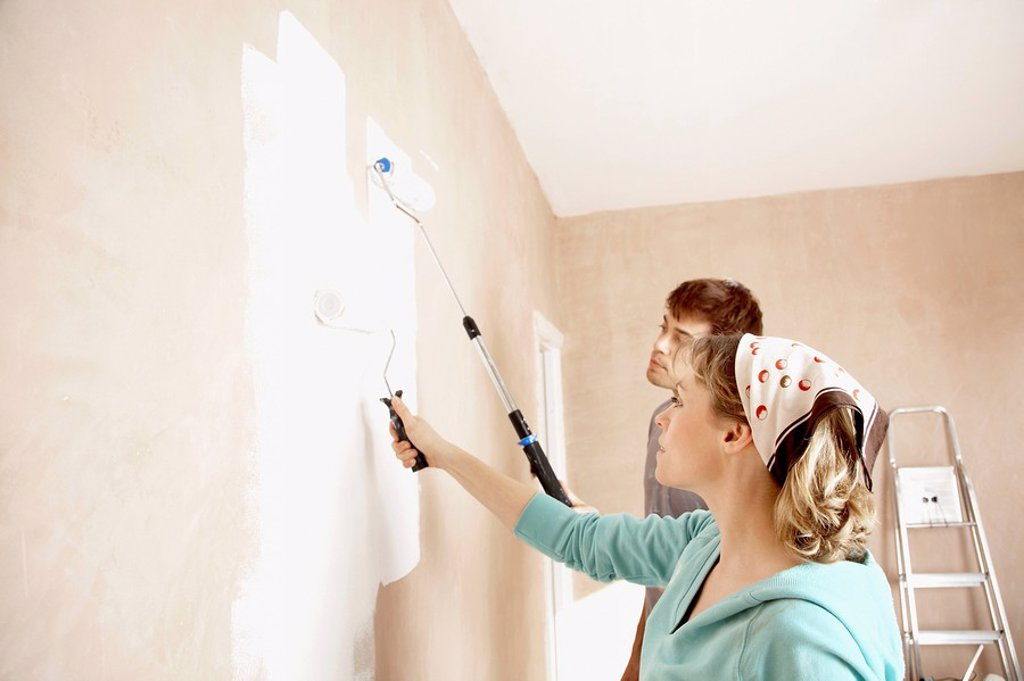 Stock Photo: 1654R-4339 Couple painting wall with paint rollers indoors
