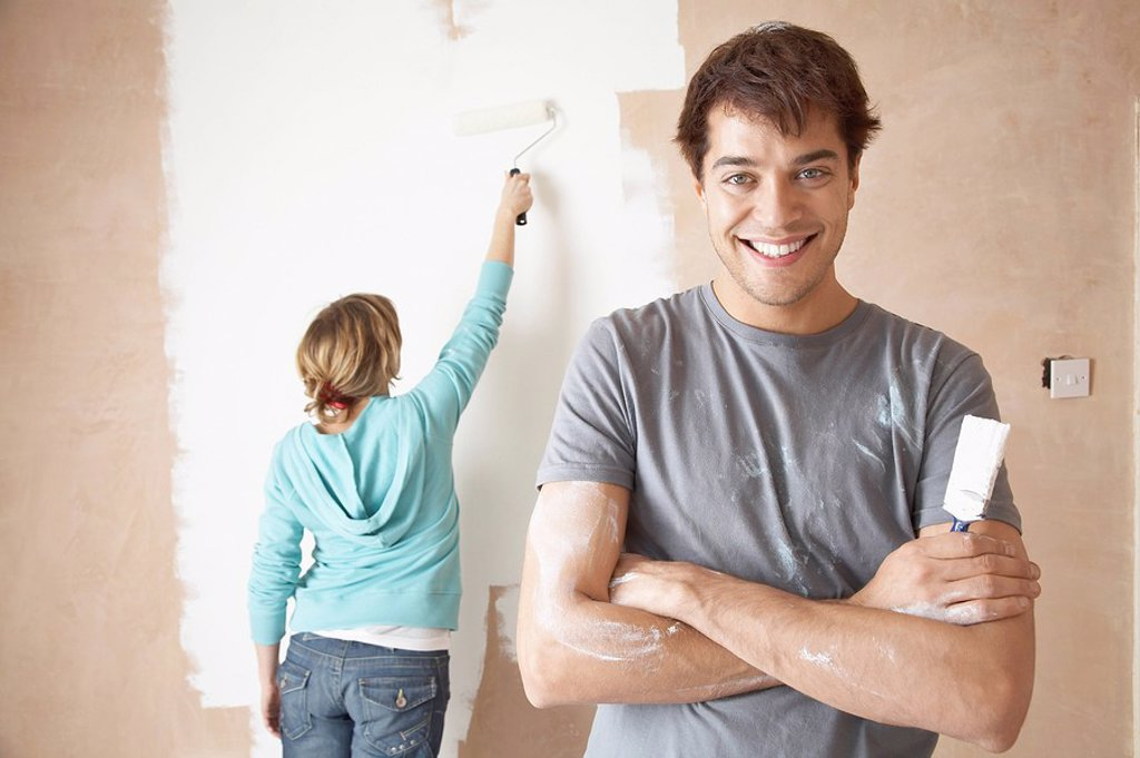Couple painting interior wall using brush and roller : Stock Photo