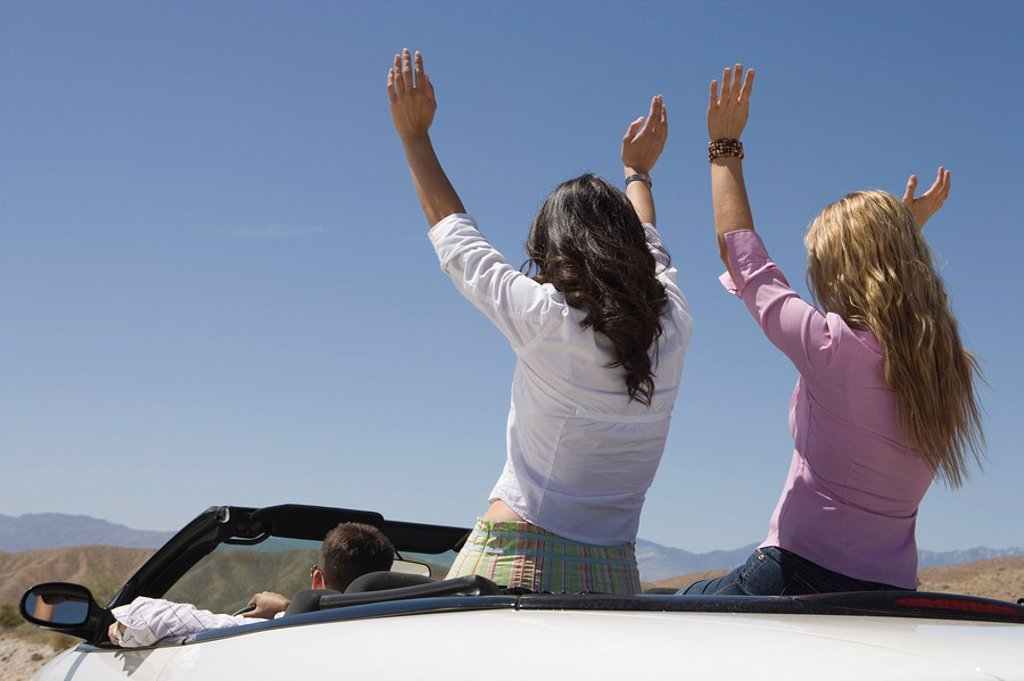 Man and two young women raising arms in car : Stock Photo