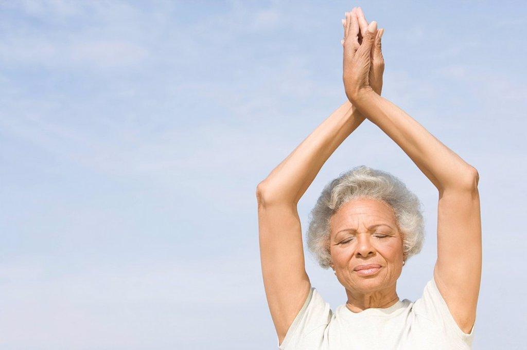 Senior woman with eyes closed in yoga pose : Stock Photo