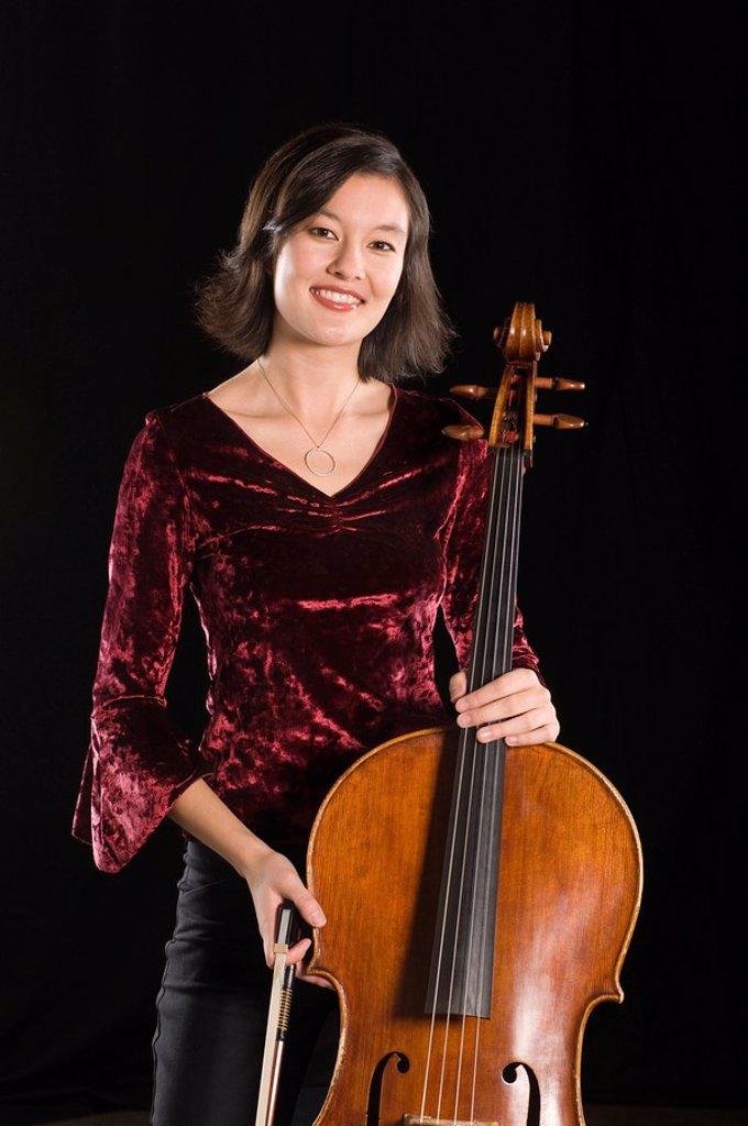 Stock Photo: 1654R-44035 Female cellist stands with cello portrait