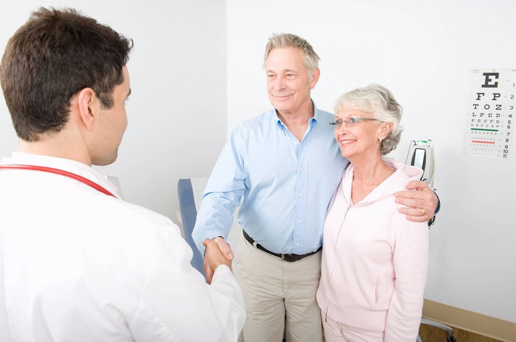 Mid adult doctor shaking hand of senior man in couple : Stock Photo