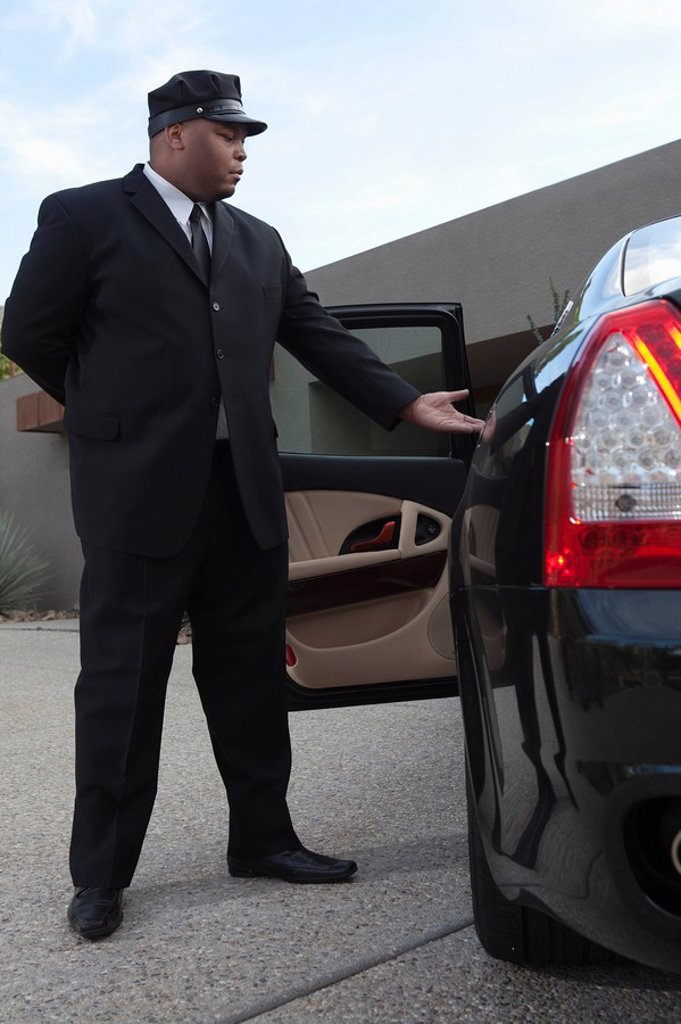 Chauffeur extends hand to client in luxury vehicle : Stock Photo
