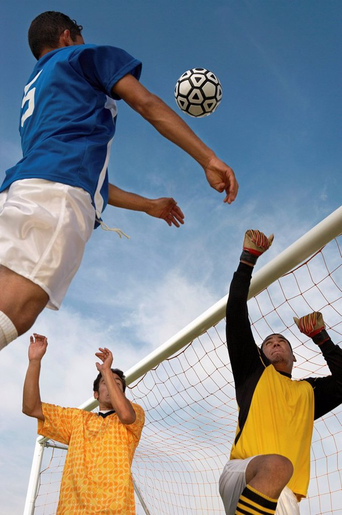 Soccer players jumping for ball : Stock Photo