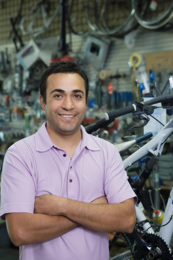 Stock Photo: 1654R-45348 Bike shop assistant stands with arms folded