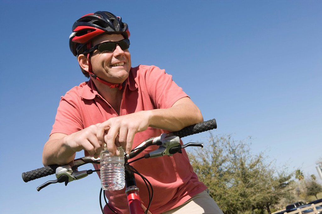 Mature man in cycling helmet leans on bicycle handlebars : Stock Photo