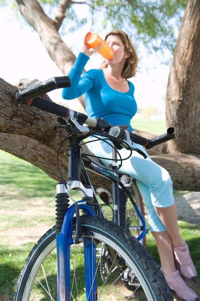 Stock Photo: 1654R-45391 Mature woman drinking water on a tree with her bike