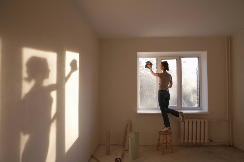 Woman cleaning windows in new apartment : Stock Photo