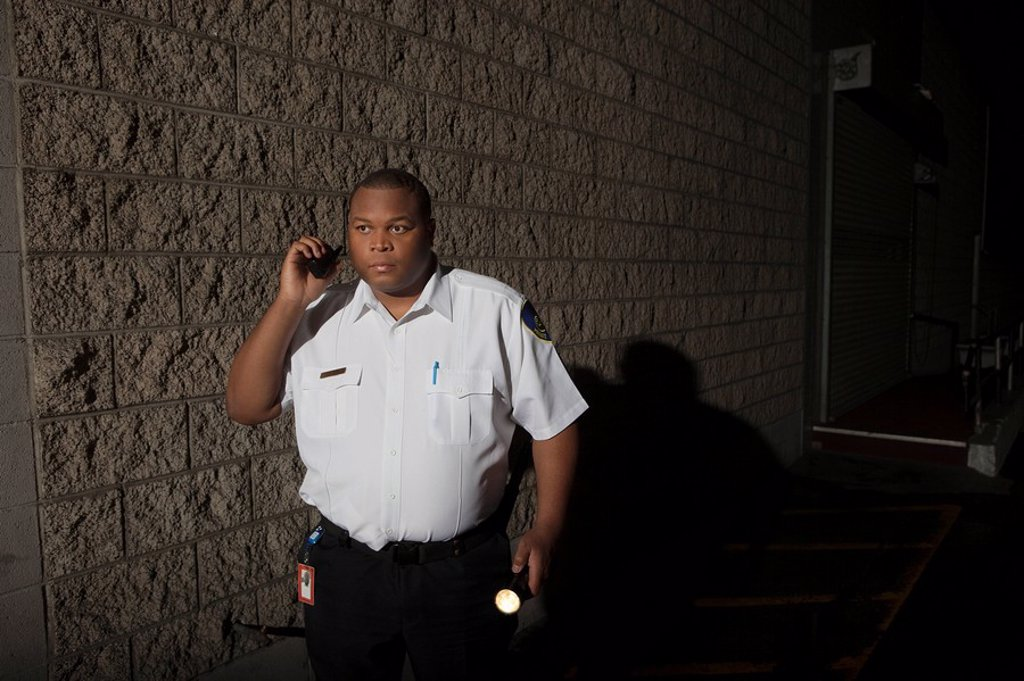 Stock Photo: 1654R-45646 Security guard patrols with torch