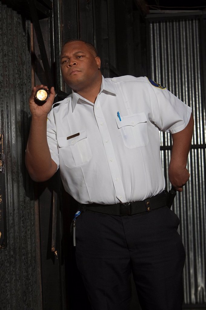 Security guard investigates with torch : Stock Photo
