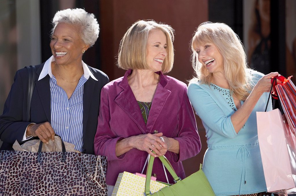 Smiling Women walking outside carrying bags on Shopping Trip : Stock Photo