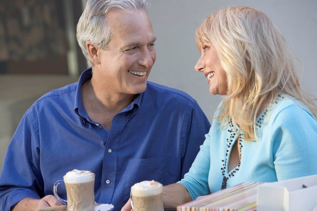 Stock Photo: 1654R-4624 middle_aged Couple sitting outdoors on Shopping Trip looking in eyes